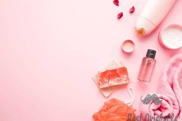 Cream jars shower bottle essential oil towel orange wisp and soap on pastel pink table. Relax products for body washing. Empty place for text quote sayings or logo. shower gel vs body wash