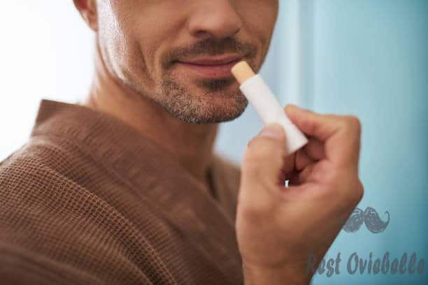 young man using hygienic lipstick on blue background - lip balm s and pictures Things To Take Into Account When Buying Best Lip Balm For Men